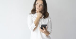 Pensive girl thinking over text message. Young Caucasian woman holding smartphone, leaning chin on hand and looking away. Reflecting and communication concept