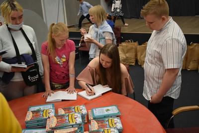 Девочка подписывает книги