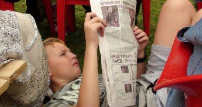 Мальчик читает газету